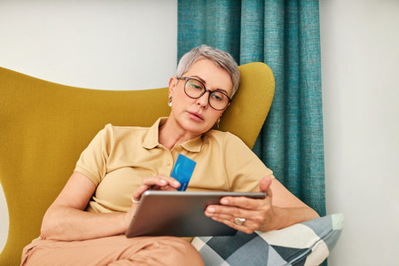 Mature woman in casuals paying by credit card while online shopping from home