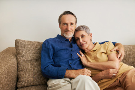 Senior couple embracing on a sofa  Affectionate people hugging at home