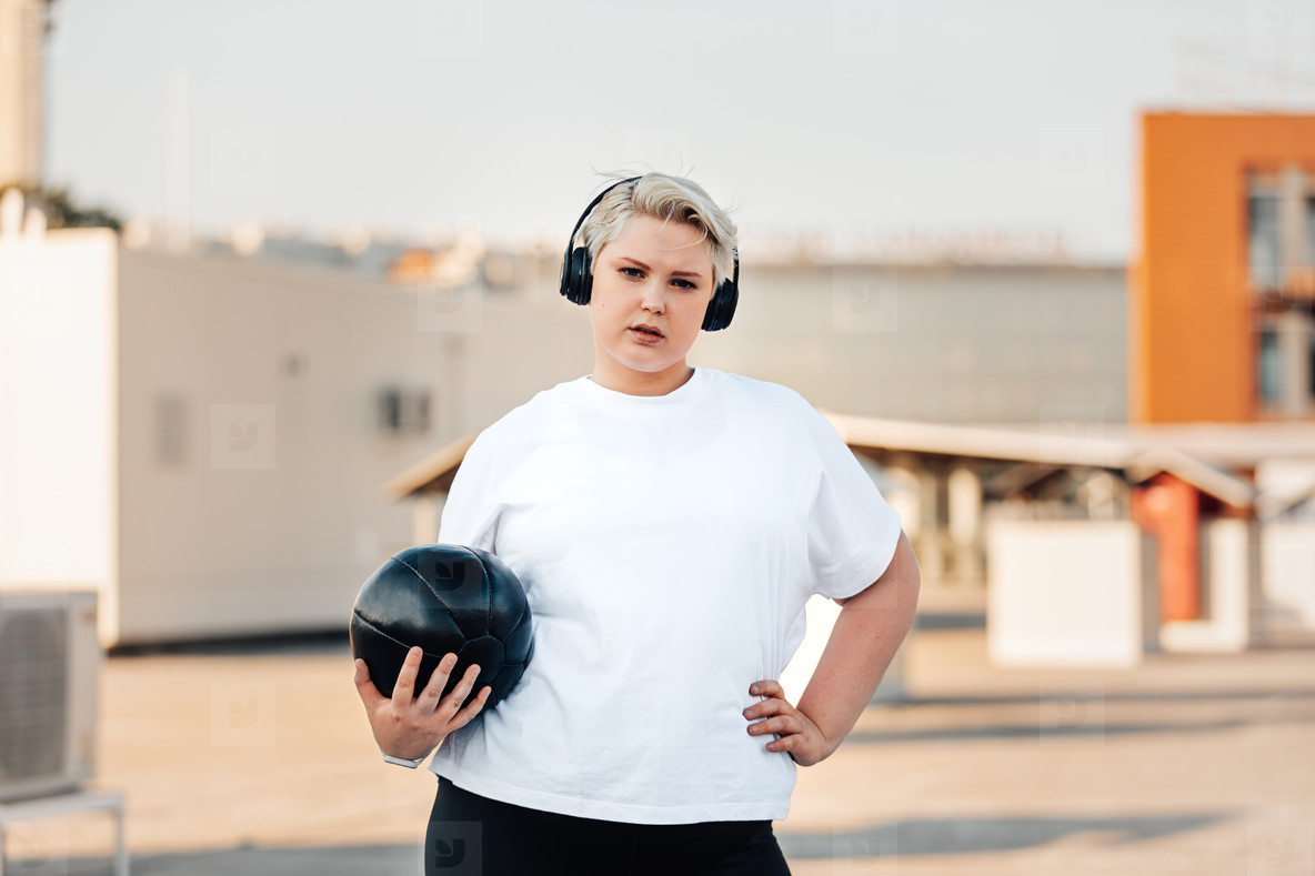 Young woman with plus size body holding a medicine ball while standing on a roof