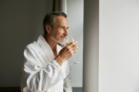 Senior man in bathrobe smell wine looking at window in hotel room
