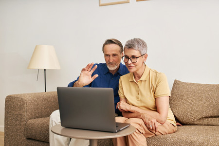 Senior couple using a laptop for video call  Mature man greeting with a hand wave while looking at a laptop