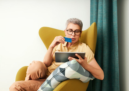Woman shopping online in living room  Mature woman with credit card and digital tablet at home