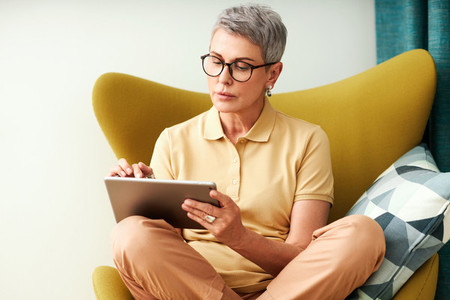 Mature woman sitting with crossed legs on armchair using a digital tablet