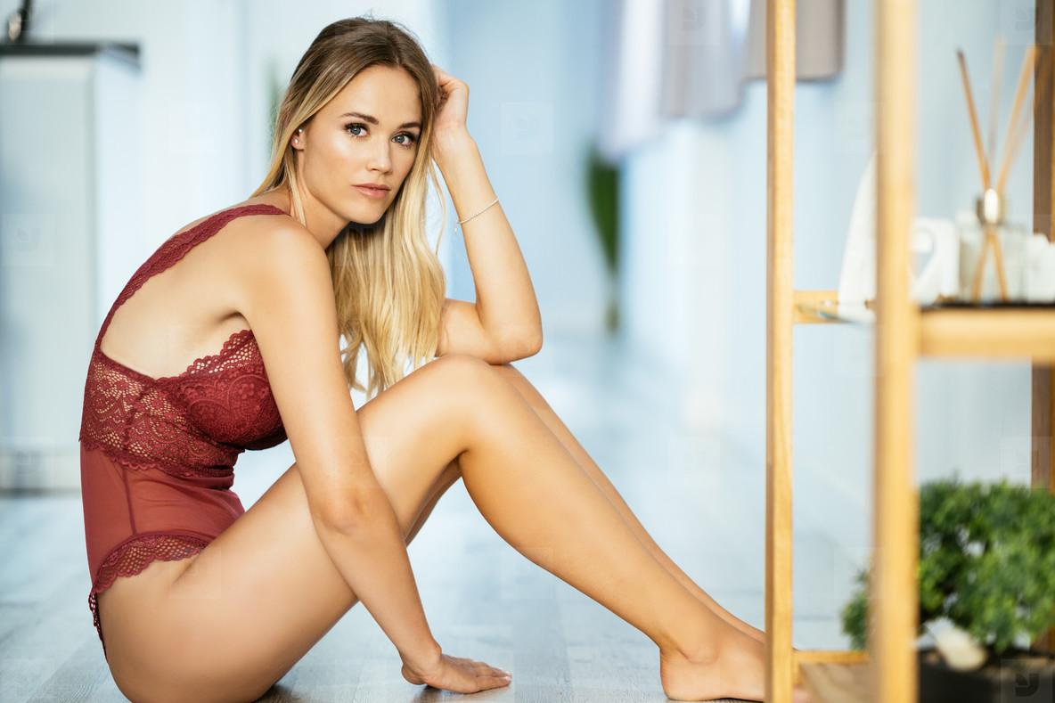 Caucasian girl in red lingerie sitting on the floor