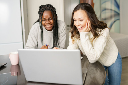 Two college girls studying together at home with laptops while drinking coffee