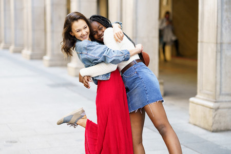Two friends happy to see each other on the street hugging