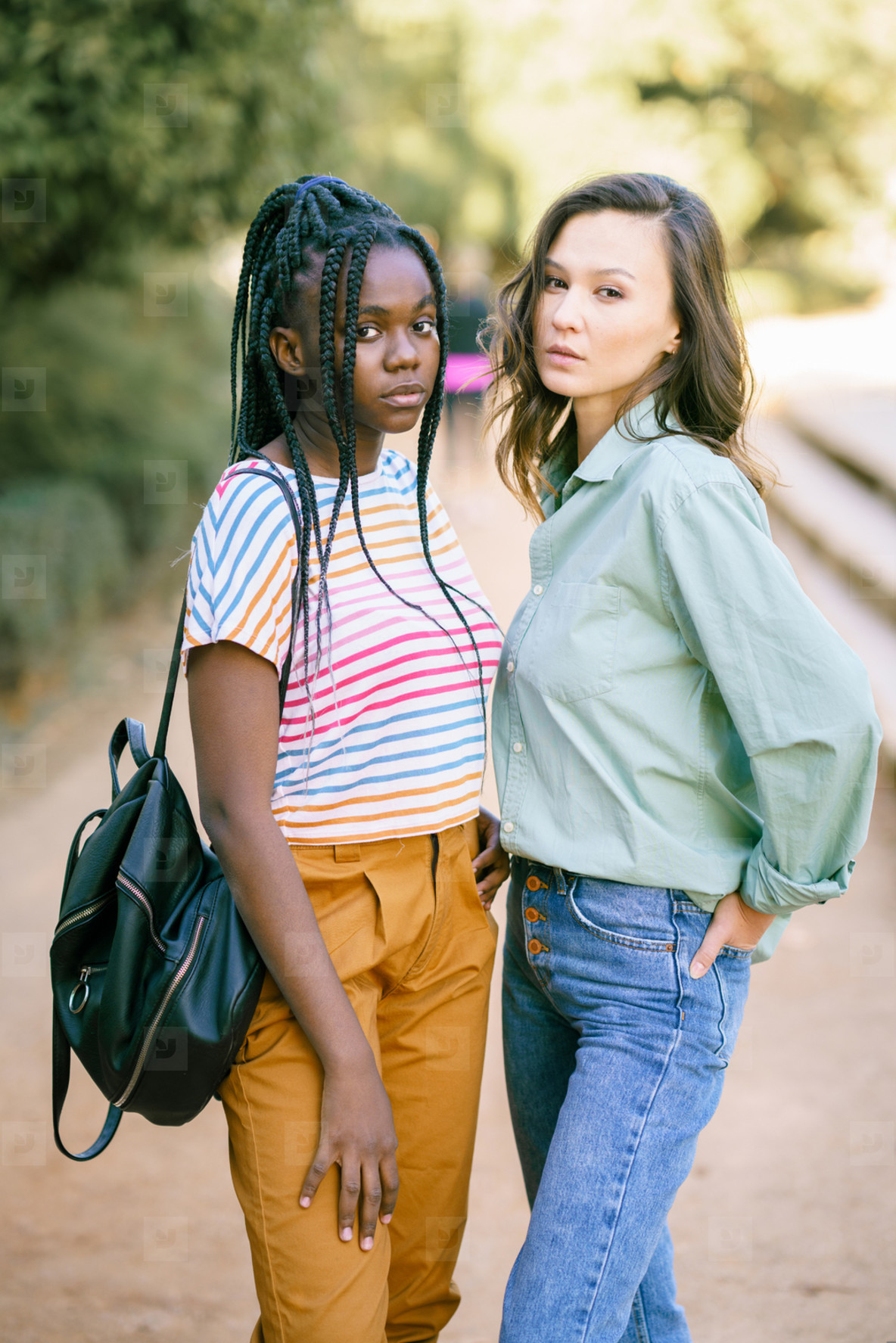 Two Multiethnic women looking at camera together on the street