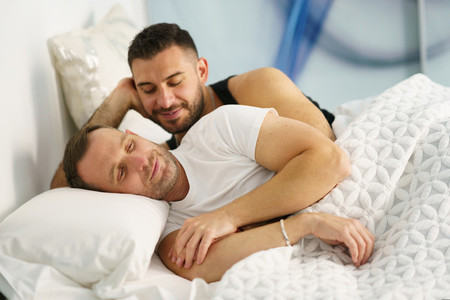 Gay couple hugging on their bed at home
