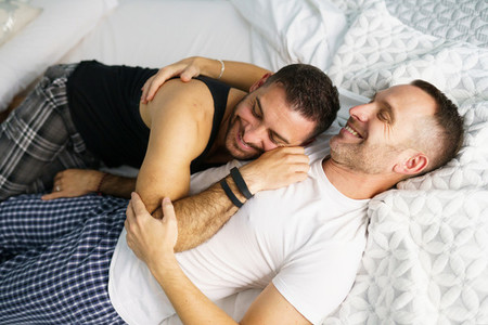 Gay couple hugging together on their bed
