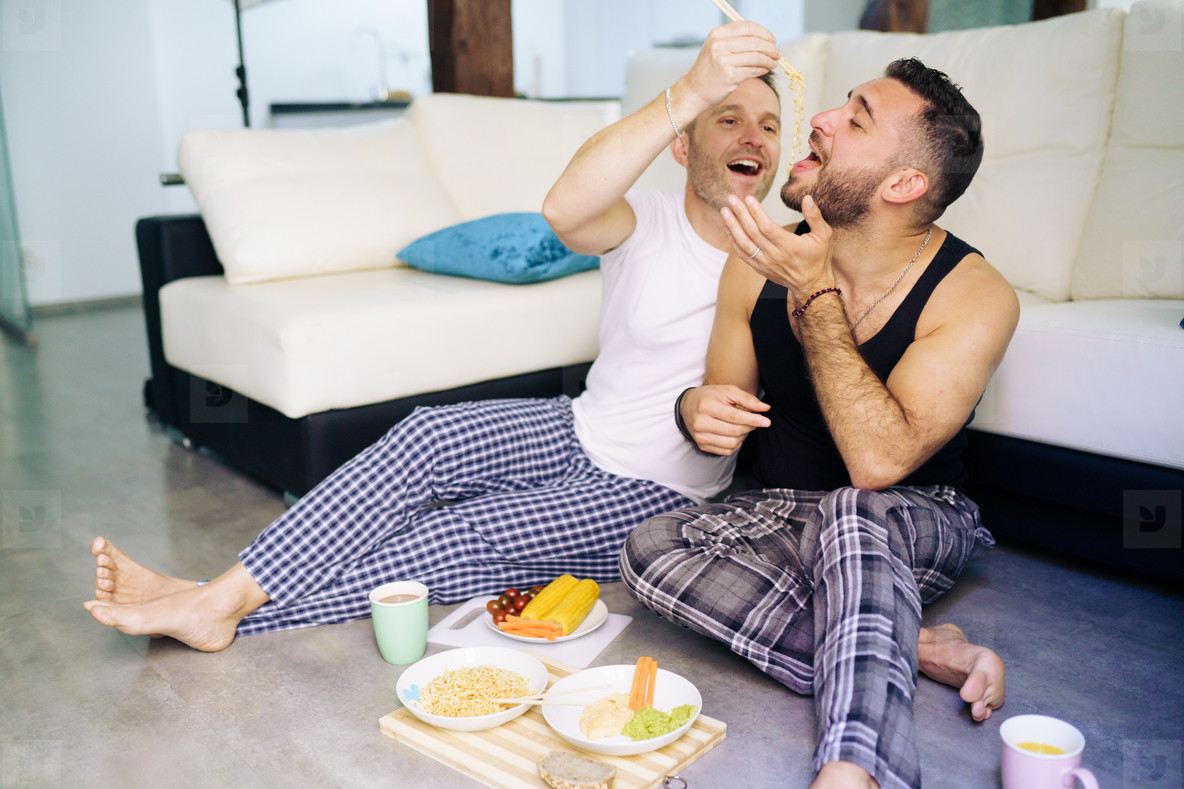 Gay couple eating together sitting on their living room floor