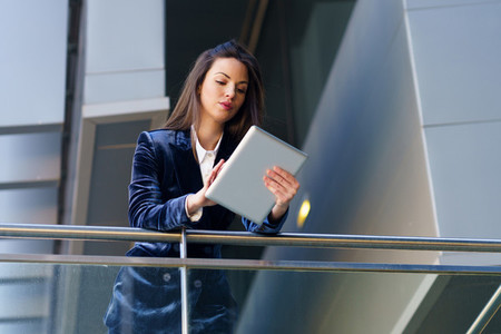 Business woman wearing blue suit using digital tablet in an office building