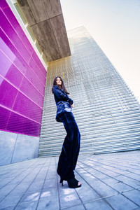 Wide angle photo of a woman wearing blue suit posing near a modern building
