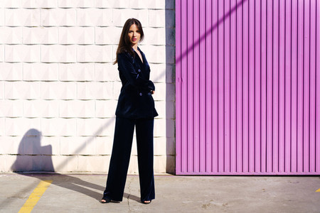 Woman wearing blue suit posing near pink shutter
