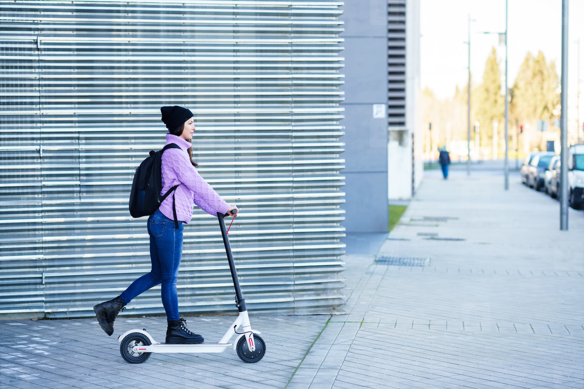Young woman in her twenties riding an electric scooter