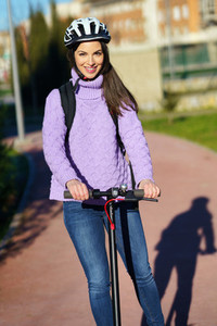 Young woman in her twenties riding an electric scooter using helmet