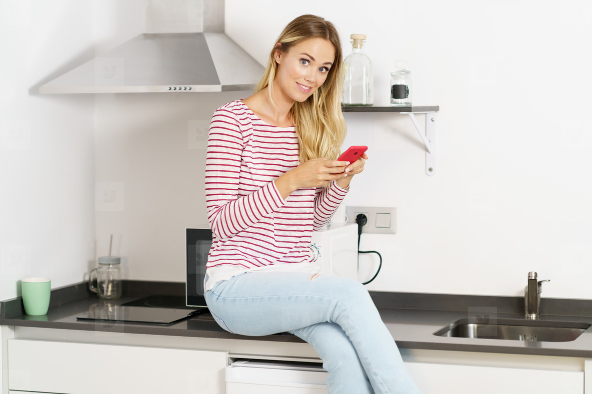 Smiling beautiful woman using her smartphone sitting in the kitchen at home