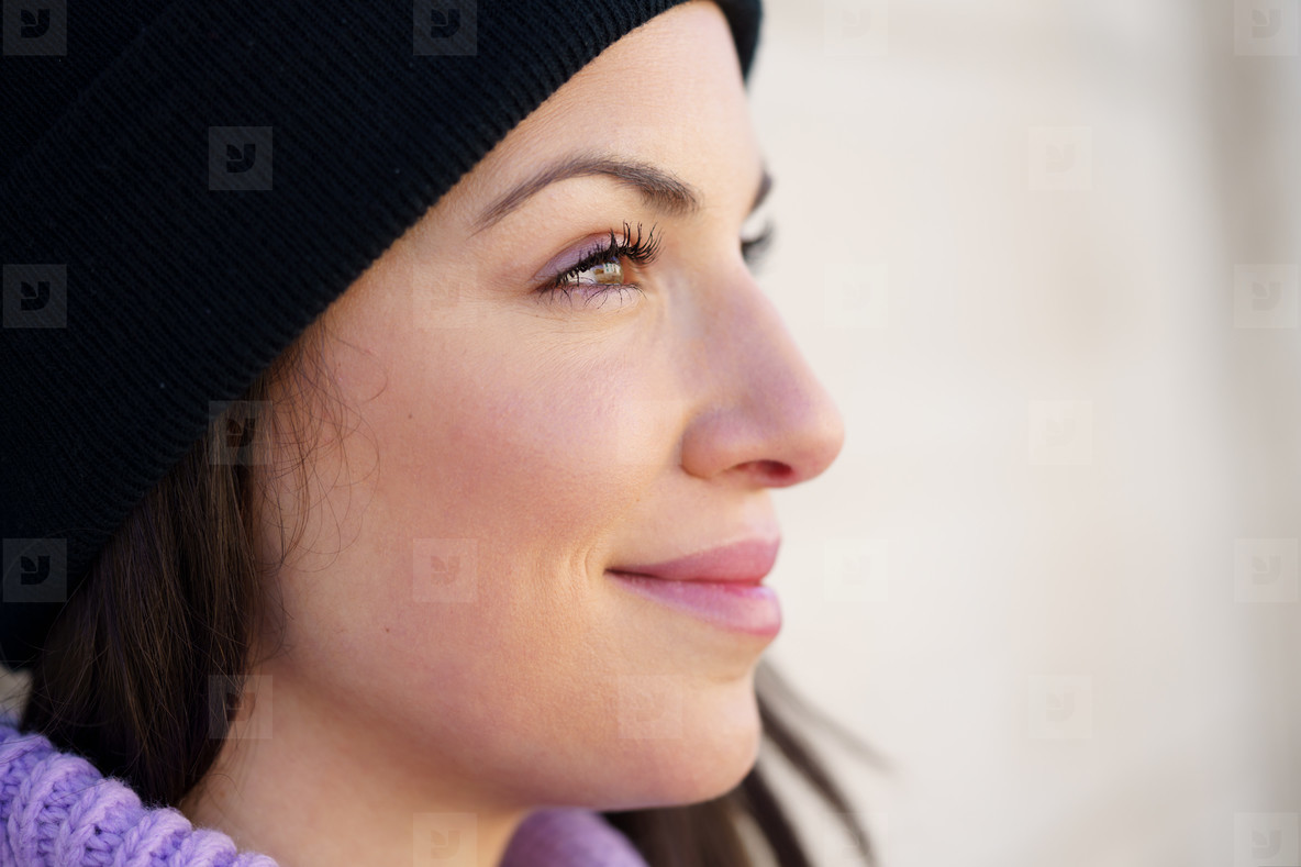 Closed portrait of young woman leaning against a wall outdoors with eyes of hope and joy