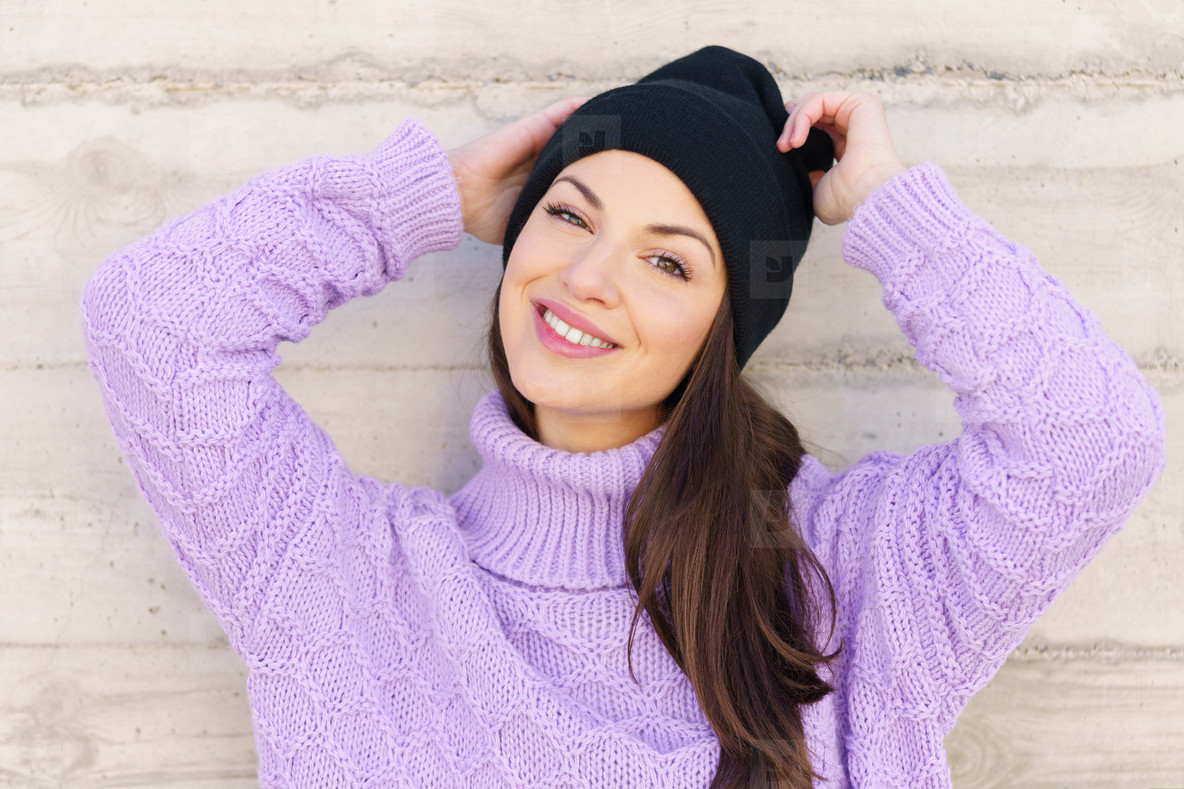 Happy young woman smiling outdoors against urban wall