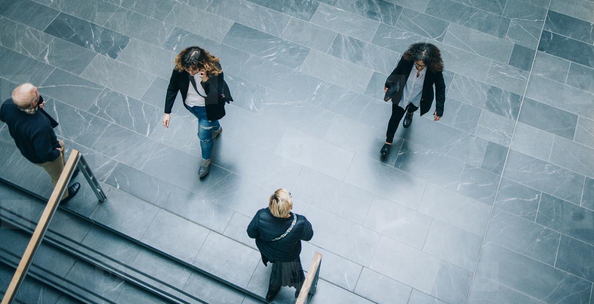 Corporate executives walking across office lobby