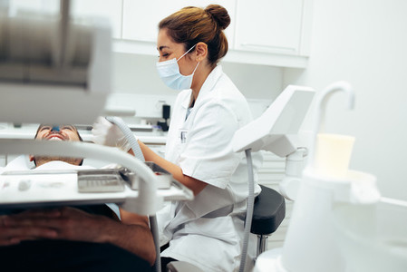 Dentist examining male patients teeth in clinic