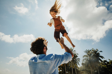 Father throwing daughter in air