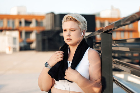 Plus size woman leaning railing on roof  Curvy tired female standing outdoors with a black towel around her neck