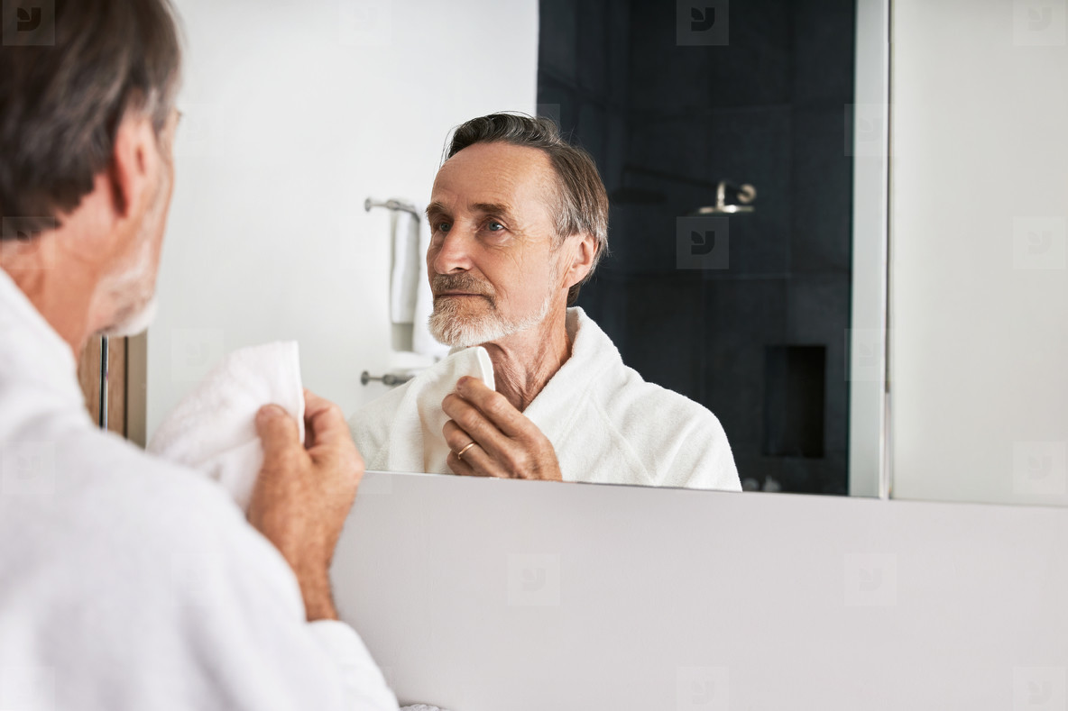 Mature man with beard holding a white towel doing morning skincare routine in the bathroom