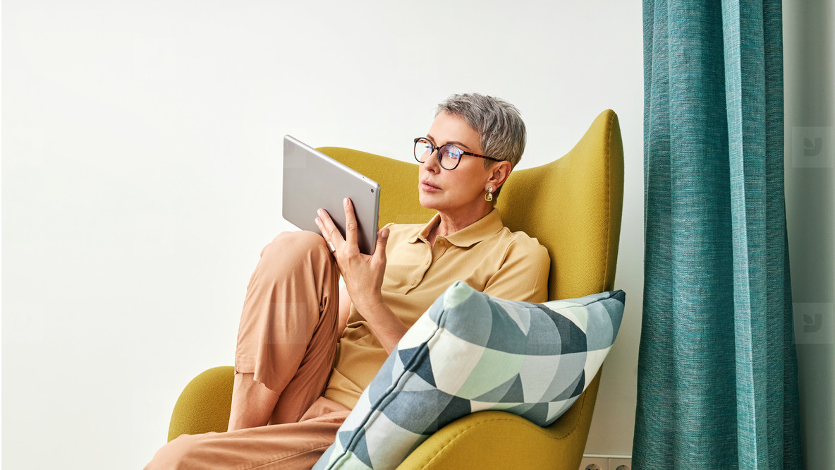 Stylish senior woman relaxing at home reading from digital tablet