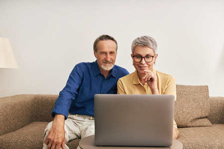Elderly couple sitting in front of a laptop in a living room communicating during a video call