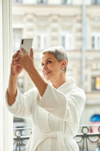 Smiling mature woman in bathrobe taking a selfie while standing on a balcony