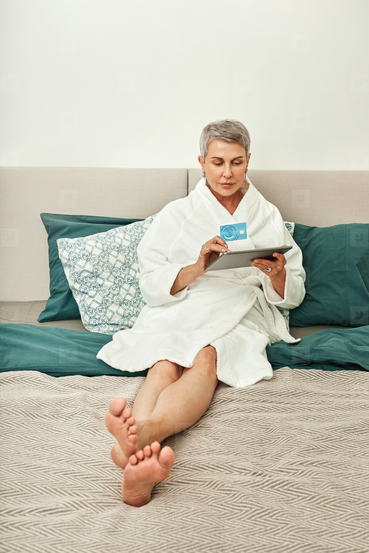 Mature woman in bathrobe lying on a bed holding a digital tablet and credit card  Senior female ordering from a hotel room