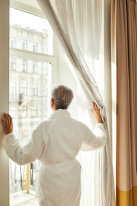 Back view of mature woman in bathrobe pulls the curtain and looks out while standing in hotel room