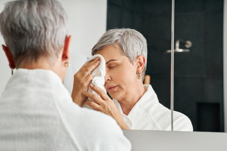 Mature woman standing in front of a mirror in bathroom doing a morning skincare routine