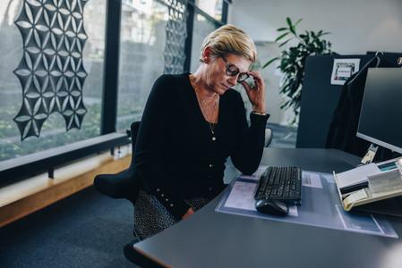 Senior businesswoman looking tired at work