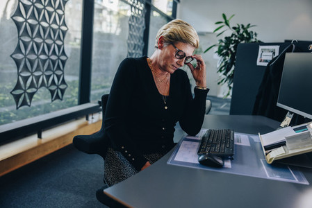 Senior businesswoman looking tired at work