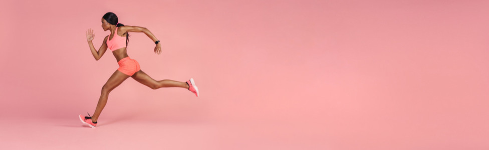 Sportswoman sprinting on a large pink background