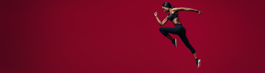 Fitness woman running over red background