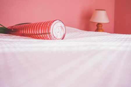 Vase leaning on a white bed