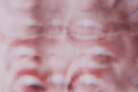 Distorted image of a young woman face view througn a prism