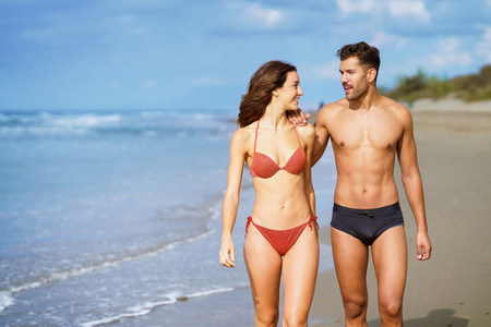 Young couple of beautiful athletic bodies walking together on the beach