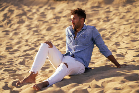 Attractive man sitting on the sand of the beach