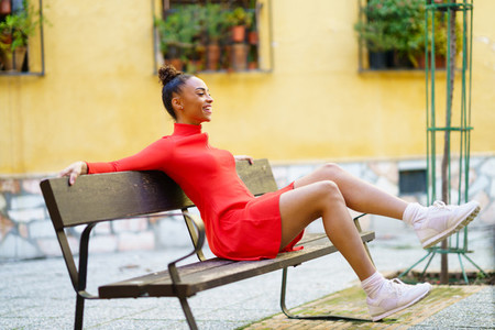 Happy mixed woman waving her legs in joy sitting on a bench in the street