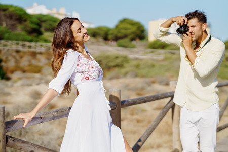 Man photographing his girlfriend on a lovers trip