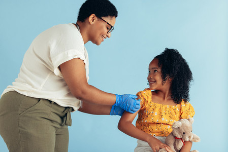 Doctor giving vaccine to small patient