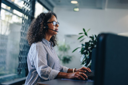 Business professional with headset working at her desk