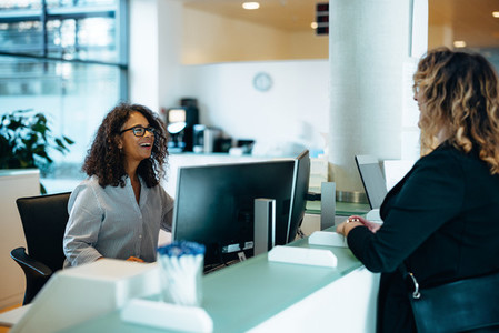 Friendly administrator assisting woman at reception desk