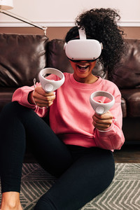Young woman having fun and playing video games with VR set in living room