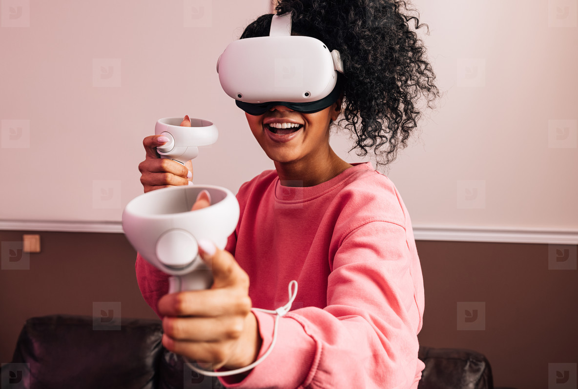 Young smiling woman using VR set while standing in living room  Female in casuals having fun with virtual reality games