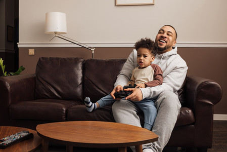 Father and son playing a video game together at home  Young man and little boy sitting on sofa holding joysticks and having fun