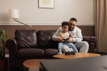 Little boy sitting on the hip of his father and holding a joystick  Male helping a kid to play a video game